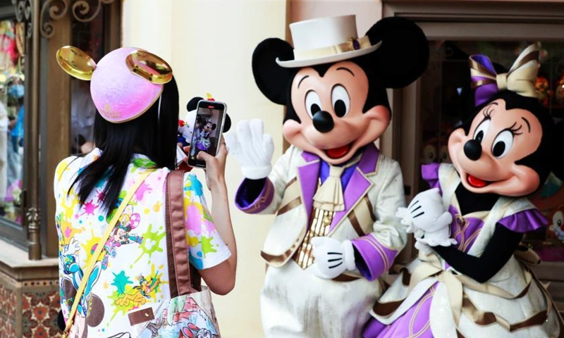A visitor interacts with Mickey and Minnie at Shanghai Disney Resort, June 16, 2021. (Photo/ Tang Yanjun)